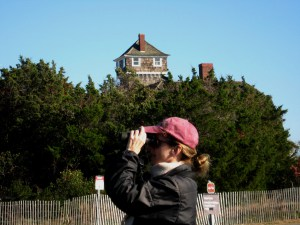 Jeanette Hooban in quest of migrant warblers, Lifesaving Station of Sandy Hook in Background